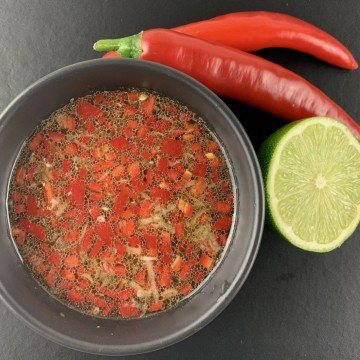 VIETNAMESE SALAD DRESSING IN BLACK BOWL WITH RED CHILLIES AND CUT LIME ON THE SIDE