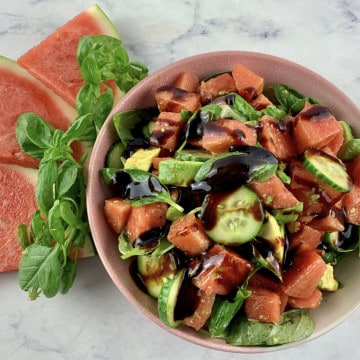 WATERMELON AVOCADO SALAD WITH BALSAMIC GLAZE IN A PINK BOWL WITH WATERMELON SLICES & BASIL ON THE SIDE