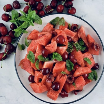 WATERMELON FRUIT SALAD ON A PLATTER WITH CHERRIES AND MINT ON THE SIDE