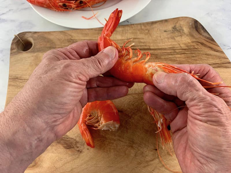 hands removing the head of a cooked prawn on wooden board
