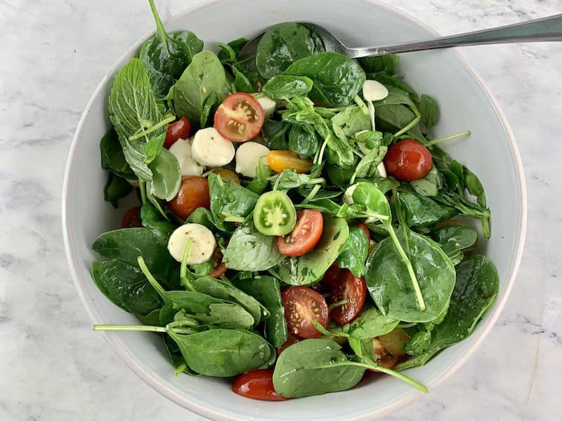 MIXING SPINACH CAPRESE,SALAD IN A WHITE WITH SPOON
