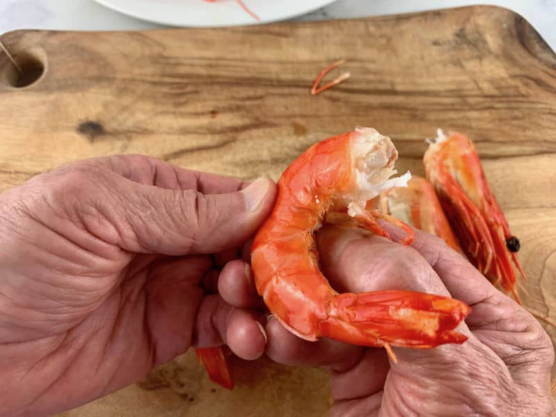 hands removing the legs of a cooked prawn on wooden board