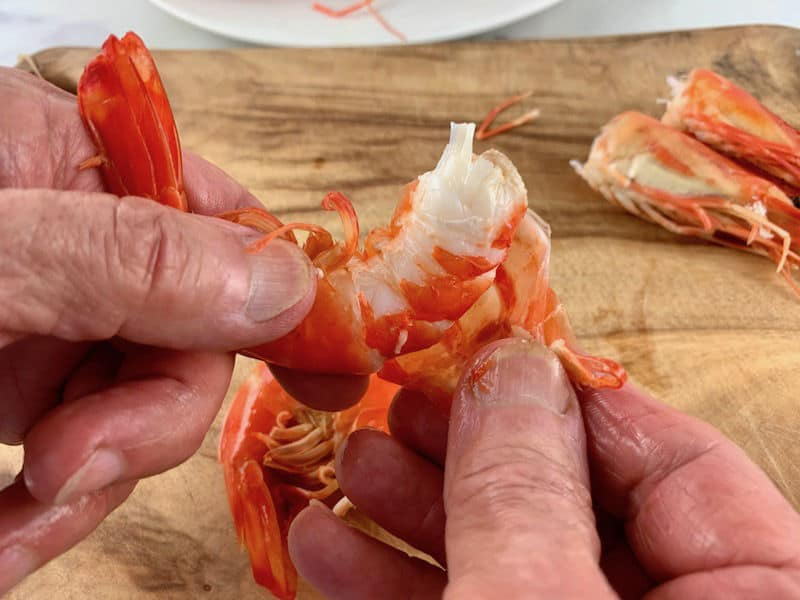 hands peeling the shell of a cooked prawn on wooden board