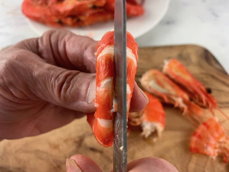 hands slitting the back of a cleaned prawn with a knife