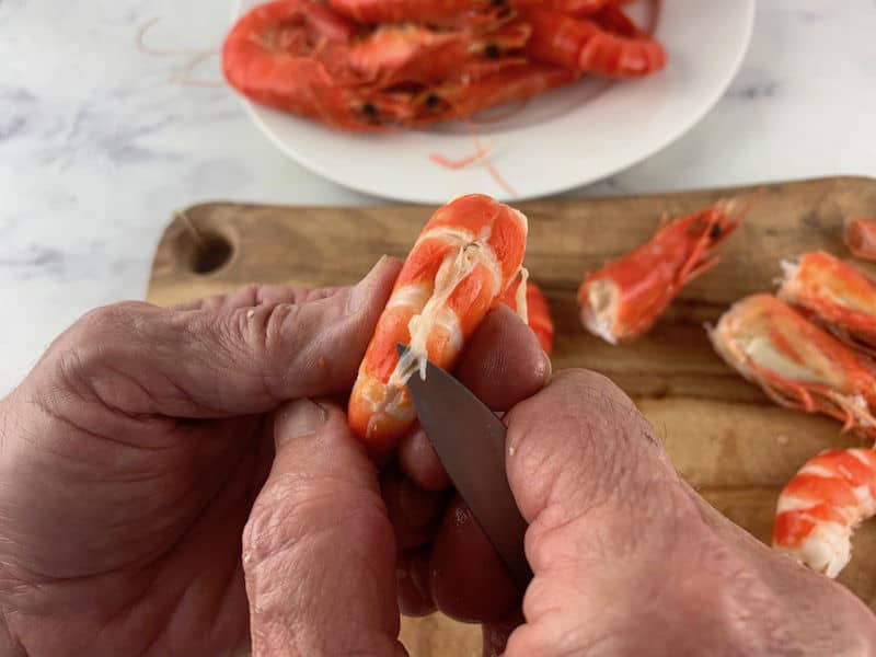 hands pulling out the vein of a cooked prawn with a knife
