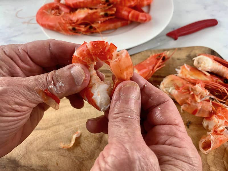 hands squeezing the tail of a cooked prawn to remove it