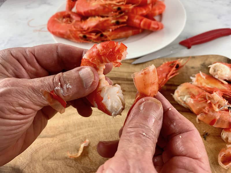 hands pulling the tail of a cooked prawn to remove it