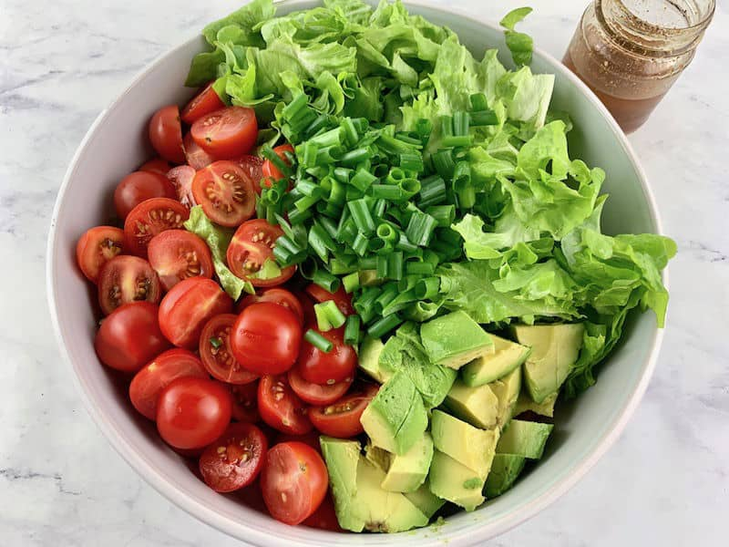 CAJUN SHRIMP SALAD INGREDIENTS IN WHITE BOWL WITH DRESSING ON SIDE