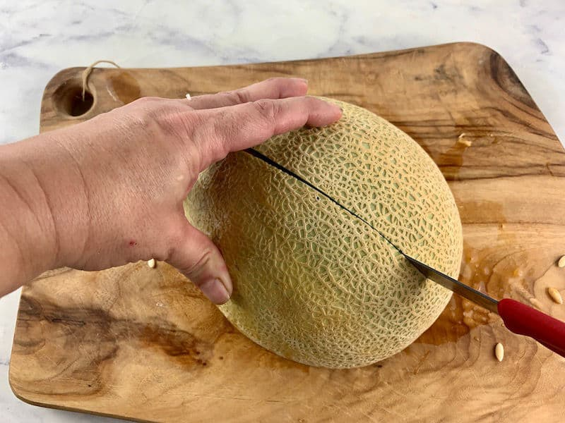 HALF MELON ON BOARD WITH HANDS CUTTING IT IN HALF WITH A KNIFE