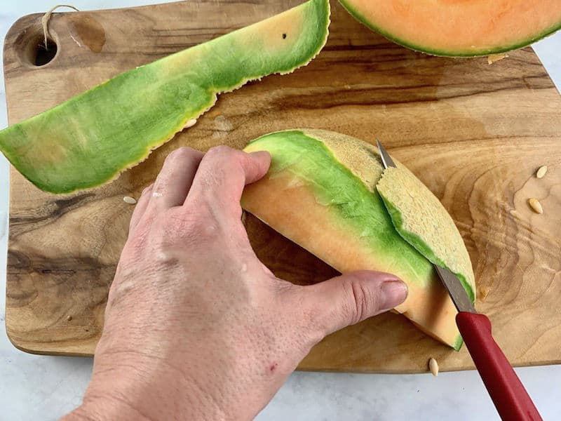 HANDS USING A KNIFE TO PEEL A MELON