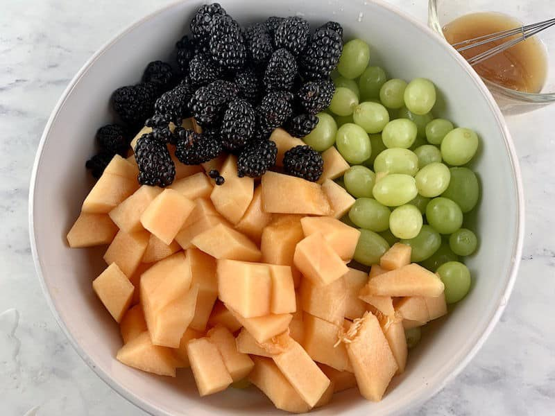 CANTALOUPE SALAD INGREDIENTS IN WHITE BOWL WITH DRESSING IN BACKGROUND