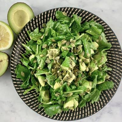 ARUGULA AVOCADO SALAD ON BLACK PATTERNED PLATE WITH AVOCADO HALVES AND LEMON ON THE SIDE