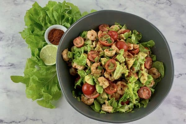 CAJUN SHRIMP SALAD IN A DARK GREY BOWL WITH LETTUCE LIME & CAJUN SPICE ON THE SIDE