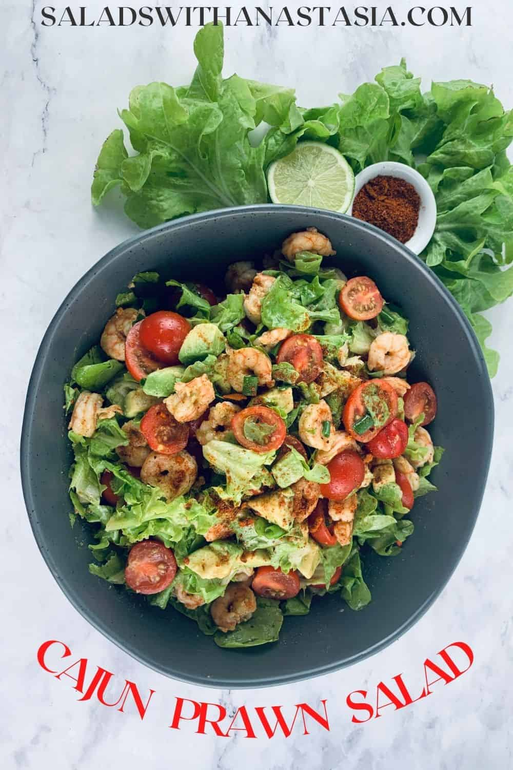 CAJUN SHRIMP SALAD IN A DARK GREY BOWL WITH LETTUCE LIME & CAJUN SPICE ON THE SIDE + TEXT OVERLAY