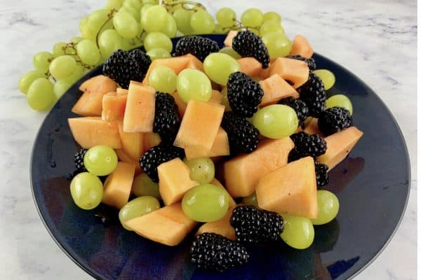 CANTALOUPE SALAD IN NAVY PLATE WITH GREEN GRAPES IN BACKGROUND