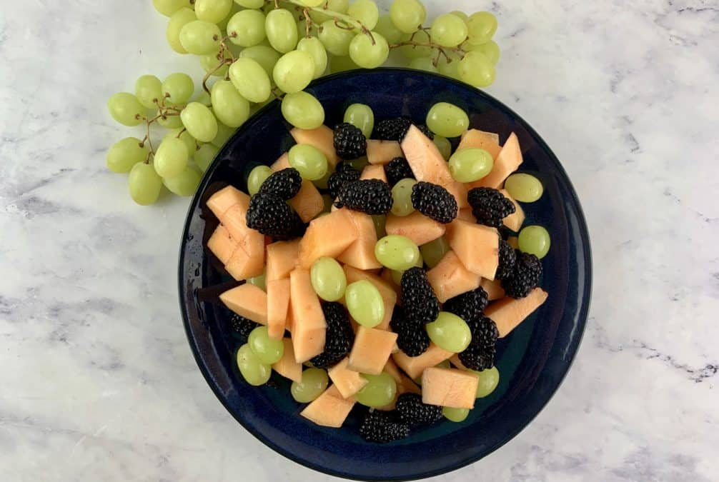 CANTALOUPE SALAD IN NAVY PLATE WITH GREEN GRAPES ON SIDE