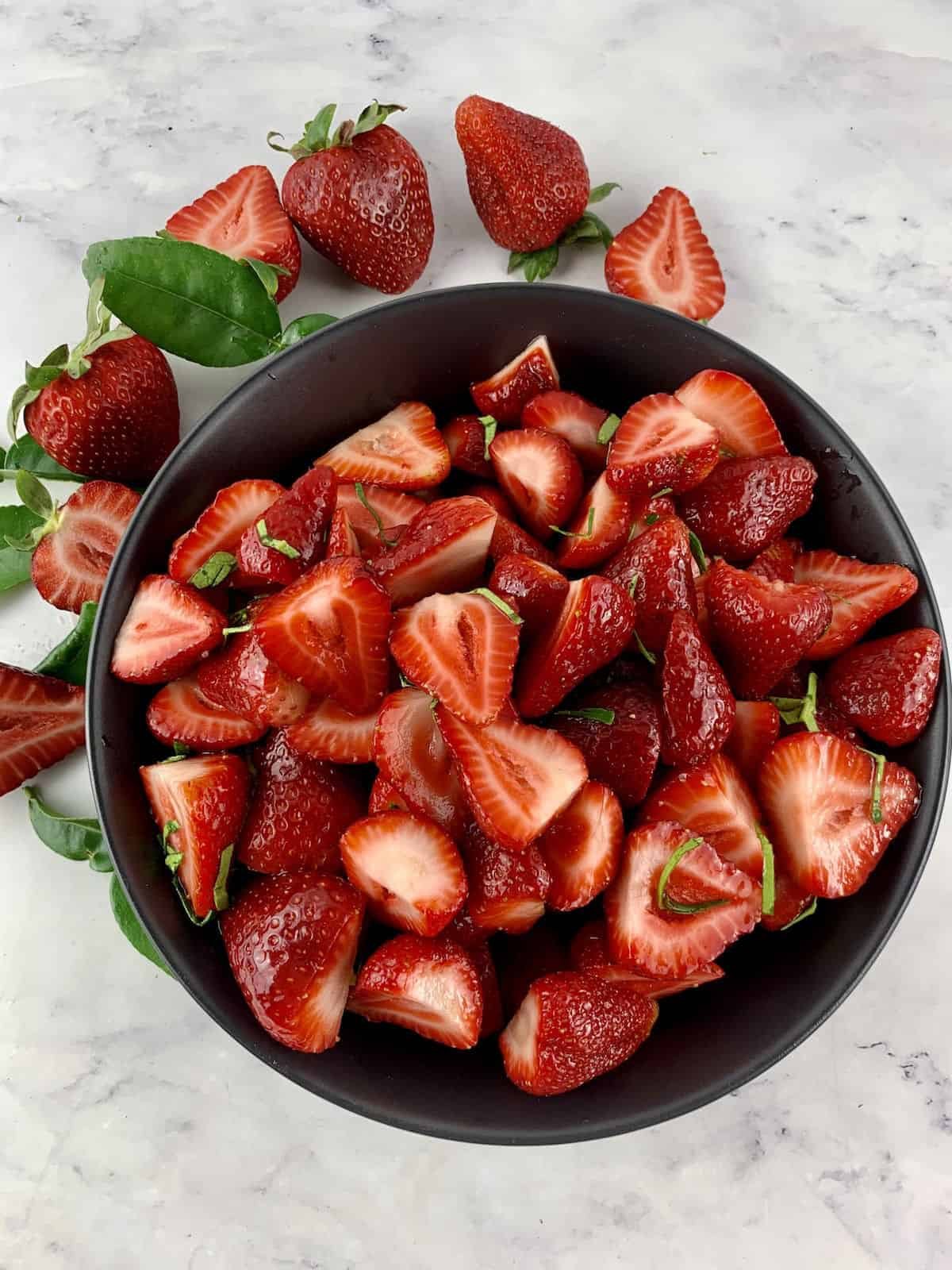 STRAWBERRIES AND LIME FRUIT SALAD IN A BLACK BOWL WITH STRAWBERRIES AND LIME LEAVES SCATTERED AROUND