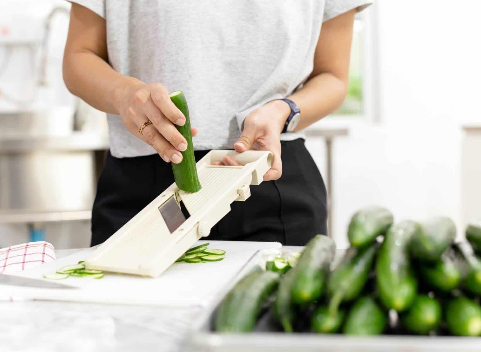 Hands using vegetable slicer to slice CUCUMBERS