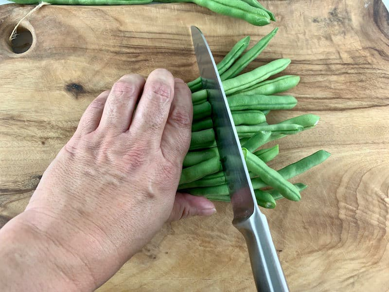 HANDS SLICING GREEN BEANS IN HALF ON WOODEN BOARD