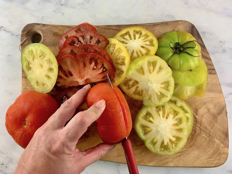 HANDS SLICING HEIRLOOM TOMATOES INTO ROUNDS