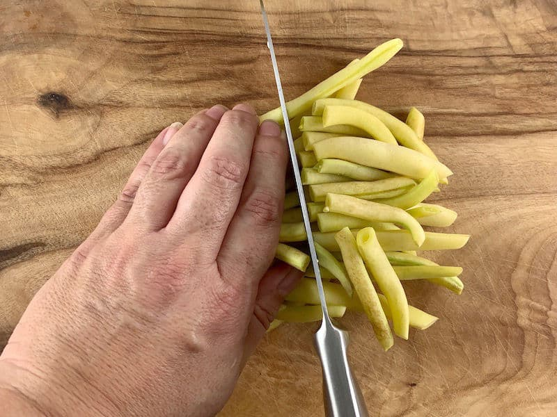 HANDS SLICING YELLOW BEANS IN HALF ON WOODEN BOARD
