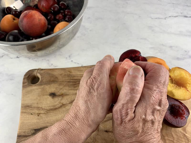 HANDS TWISTING APART WHITE PEACH WITH HALVED STONE FRUIT ON A WOODEN BOARD IN BACKGROUND