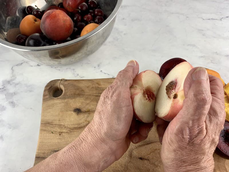 HANDS PULLING APART WHITE PEACH WITH HALVED STONE FRUIT ON A WOODEN BOARD IN BACKGROUND