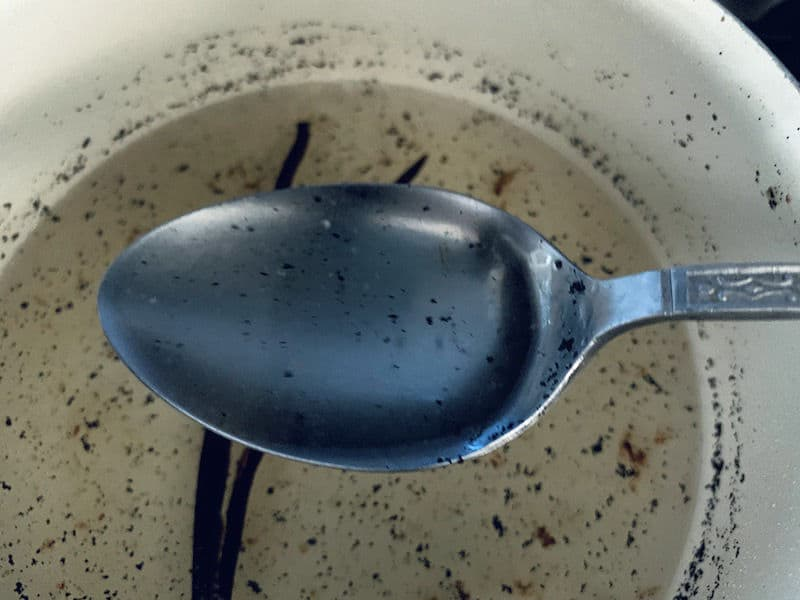 SPOON WITH VANILLA BEAN SYRUP OVER PAN SHOWING DISSOLVED SUGAR