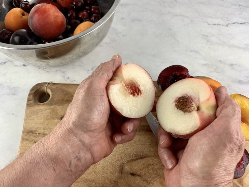 HANDS SEPARATING WHITE PEACH WITH HALVED STONE FRUIT ON A WOODEN BOARD IN BACKGROUND
