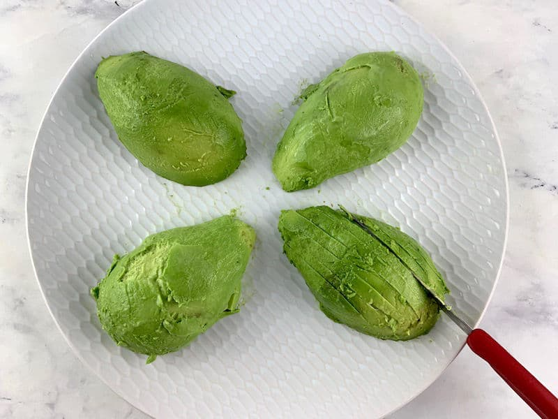 SLICING AVOCADO ON A WHITE PLATE WITH A RED KNIFE