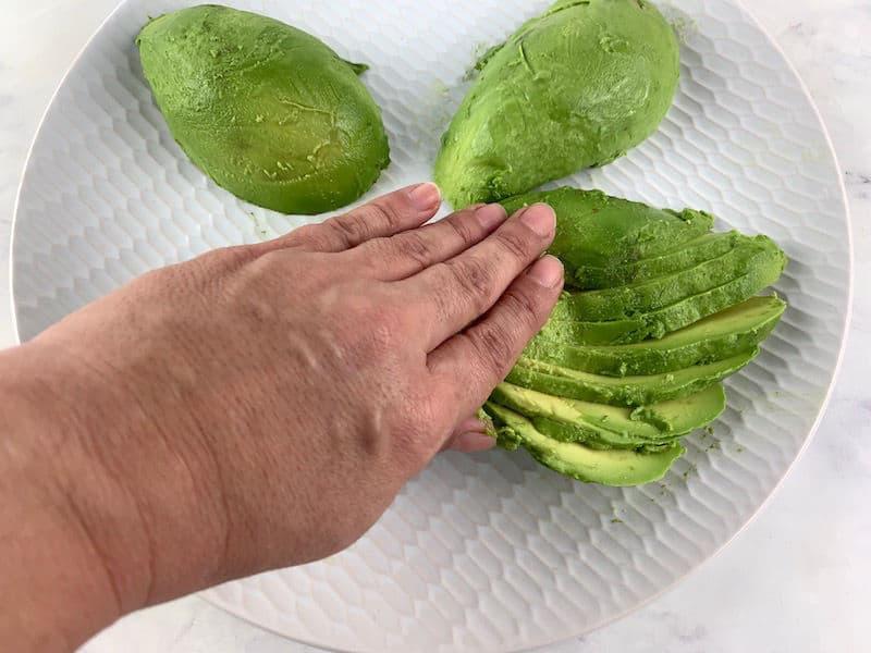 HANDS GENTLY PUSHING AVOCADO TO FAN