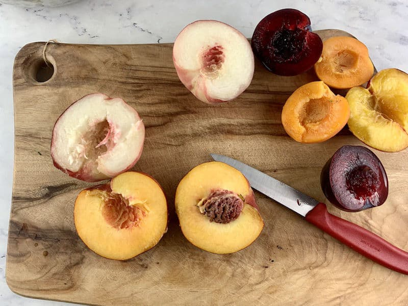 HALVED STONE FRUIT ON WOODEN BOARD WITH RED KNIFE