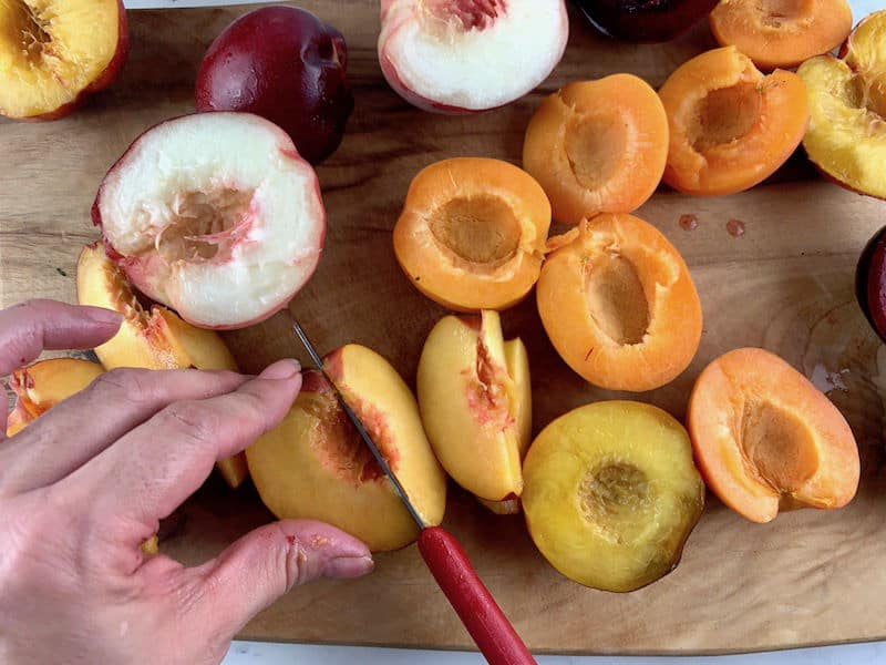 HANDS SLICING STONE FRUIT WITH A RED KNIFE ON A WOODEN BAORD