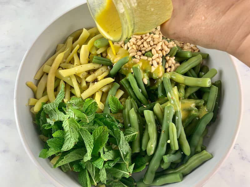 POURING OVER MUSTARD DRESSING ON YELLOW BEAN SALAD INGREDIENTS