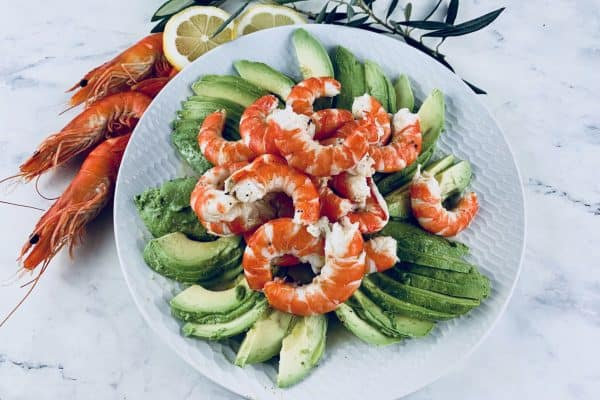 SHRIMP AND AVOCADO SALAD ON A WHITE PLATE WITH PRAWNS AND LEMON SLICES ON THE SIDE