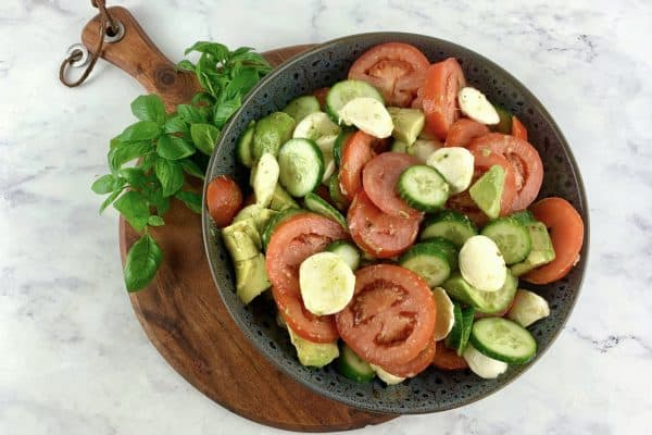 TRICOLORE SALAD IN A DARK GREY BOWL SITTING ON WOODEN BOARD WITH BASIL SPRIGS ON THE SIDE