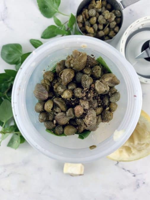 BASIL CAPER DRESSING INGREDIENTS IN BLENDER WITH INGREDIENTS SCATTERED AROUND