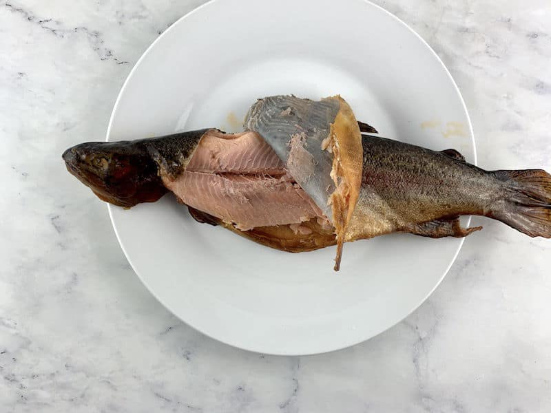 PEELING OFF TROUT SKIN ON WHITE PLATE