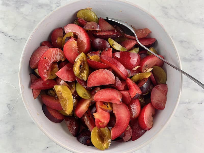 MIXING PLUMS, CARDAMOM SEEDS & SYRUP IN A WHITE BOWL WITH A SPOON