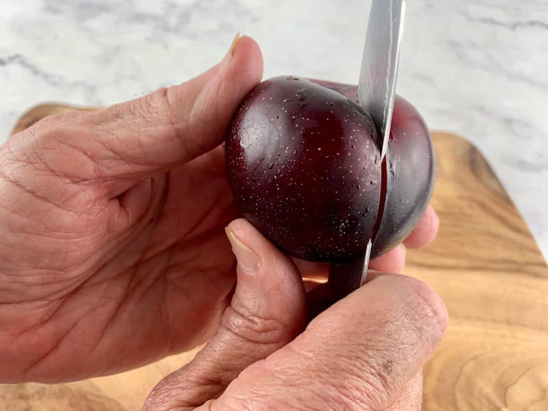 HANDS CUTTING AROUND A PLUM WITH A KNIFE ON WOODEN BOARD