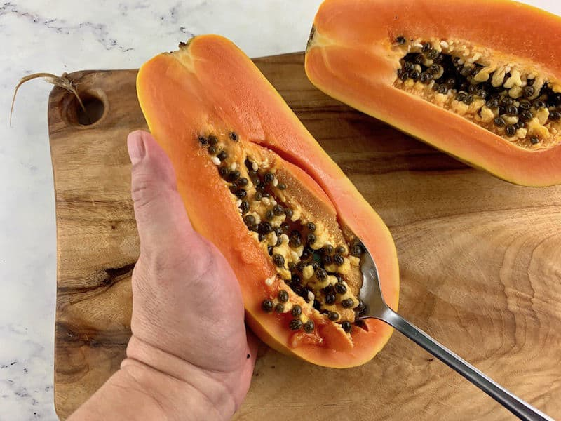 HANDS SCOOPING OUT PAPAYA SEEDS ON WOODEN BAORD