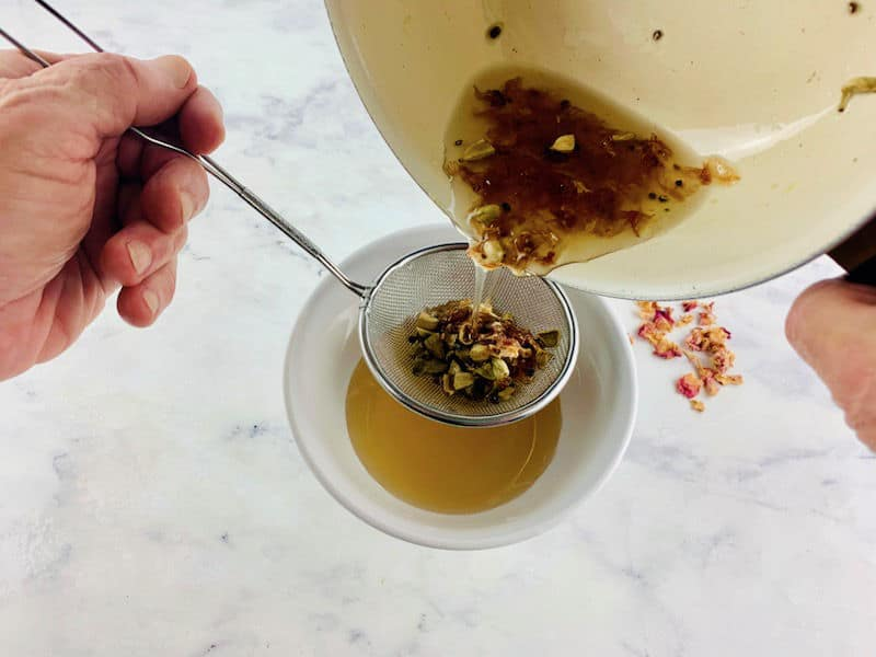 HANDS STRAINING CARDAMOM SYRUP INTO A WHITE BOWL