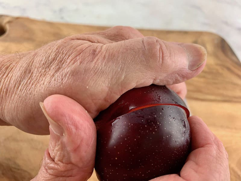 HANDS TWISTING PLUM ON WOODEN BOARD