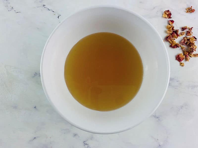 CARDAMOM SYRUP IN A WHITE BOWL WITH ROSE PETALS ON THE SIDE