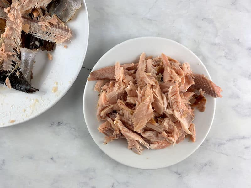 FLAKED SMOKED TROUT ON WHITE PLATE WITH BONES & SKINS ON PLATE TO THE SIDE