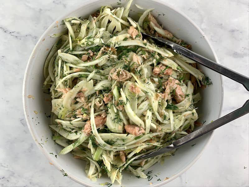 TOSSING SMOKED TROUT & FENNEL SALAD WITH TONGS IN WHITE BOWL