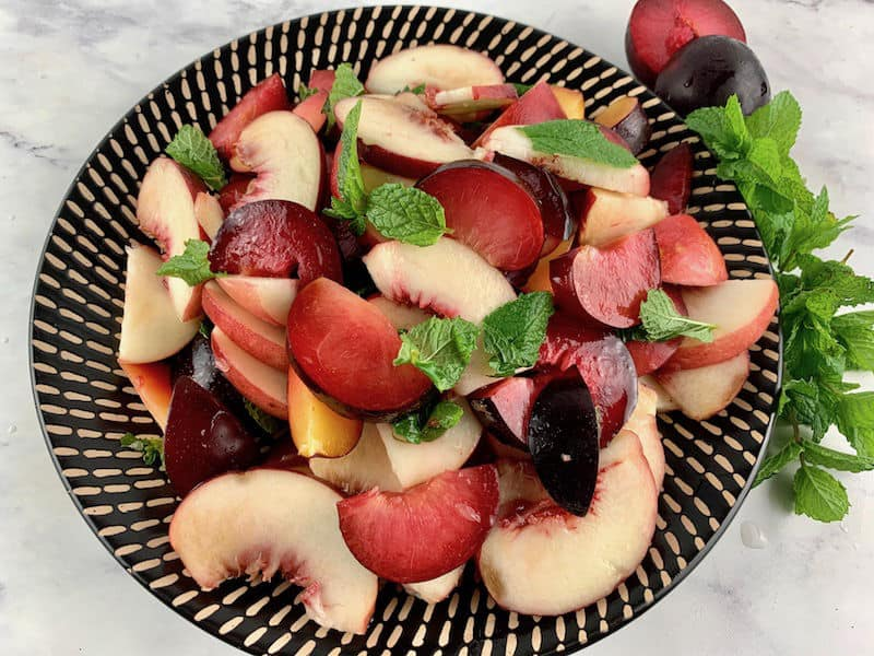 WHITE PEACH SALAD INGREDIENTS ON A BLACK PATTERNED PLATE WITH PLUMS AND MINT ON THE SIDE