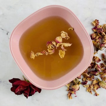 CARDAMOM SYRUP IN A PINK BOWL WITH ROSE & ROSE PETALS ON THE SIDE