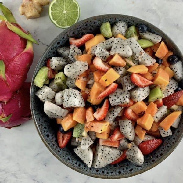 DRAGON FRUIT SALAD IN DARK GREY BOWL WITH DRAGON FRUIT, LIME & GINGER ON THE SIDE
