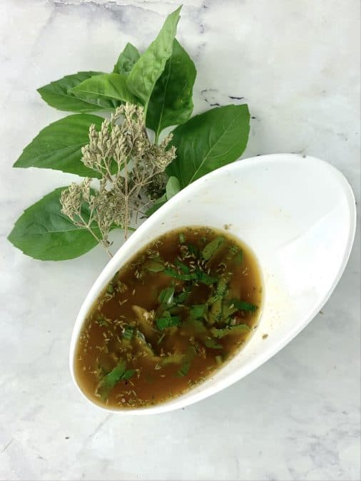 SHAKEN ITALIAN VINAIGRETTE IN A WHITE BOWL WITH FRESH BASIL AND DRIED OREGANO ON THE SIDE
